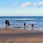 family with children by the sea in winter