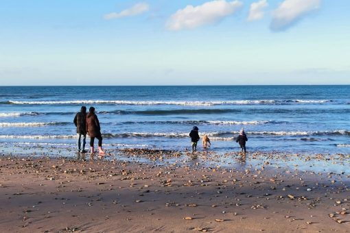 family with children on the beach in winter